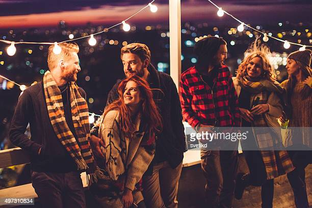 group of friends at rooftop party - roof stock photos and pictures