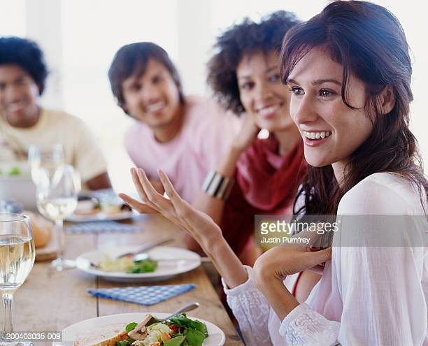 Group of friends at table (focus on young woman making hand gestures)