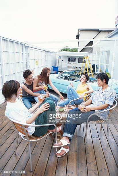 Group of friends at table with cold drinks outdoors