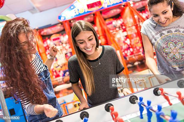 Group of friends at the amusement arcade playing foosball