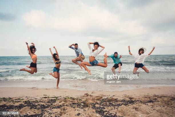 group of friends at the beach jumping from joy - free six photo stock photos and pictures