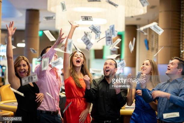 group of friends at the casino celebrating a big win throwing money to the air - spending money stock pictures, royalty-free photos & images
