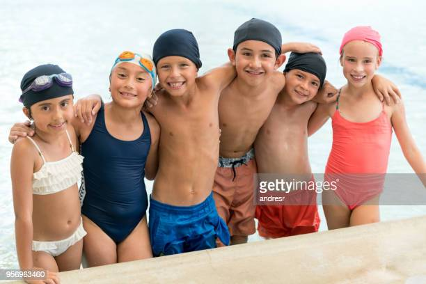 Group of friends at the pool having fun embracing each other looking at camera smiling