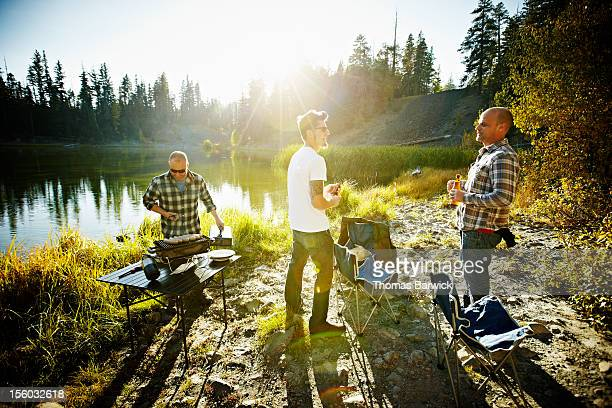 Group of friends barbecuing next to mountain lake