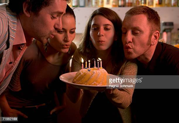 Group of friends blowing out candles on birthday cake