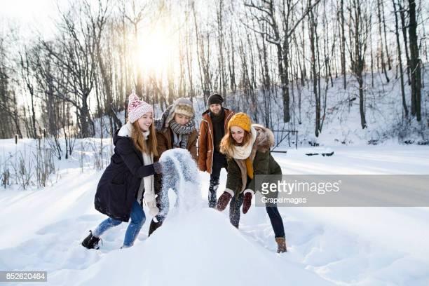 Gruppe von Freunden, die einen Schneemann bauen.