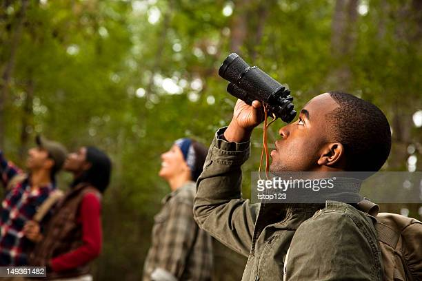Group of friends camping and hiking using binoculars. Bird watching.