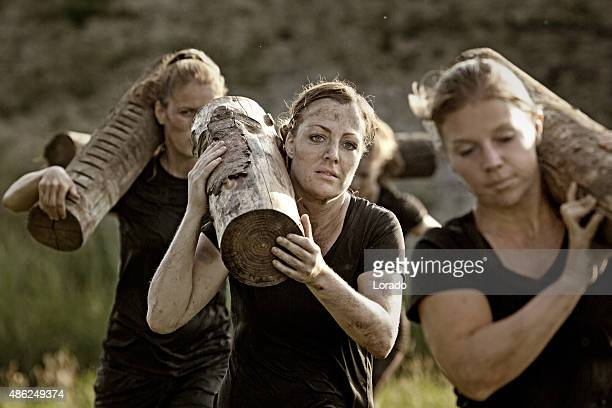 group of friends carrying wooden weights at obstacle run