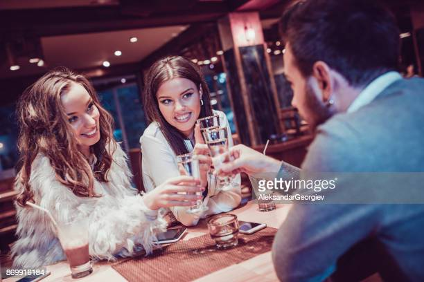 Group of Friends Celebrating at Restaurant and Toasting with Vodka