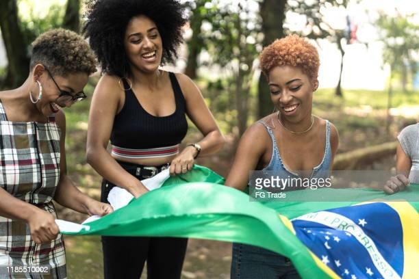ブラジルの旗を持って祝う友人のグループ - ナチュラルヘア ストックフォトと画像