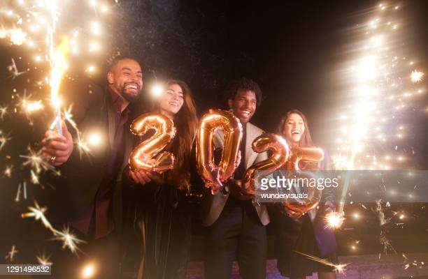 group of friends celebrating new years holding 2025 balloons and sparklers - この撮影のクリップをもっと見る 2025 stock pictures, royalty-free photos & images