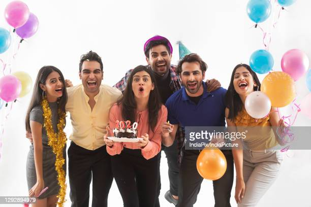 group of friends celebrating new years together with balloons and cake. - 20 29 years stockfoto's en -beelden