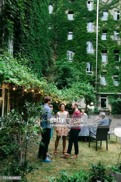 group of friends chatting after meal in courtyard - barbecue social gathering stock pictures, royalty-free photos & images