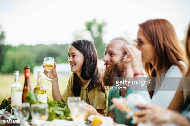 group of friends chatting and drinking at outdoor lunch - farm to table stock photos and pictures
