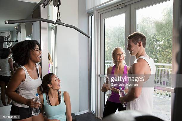 Group of friends chatting and laughing at the gym