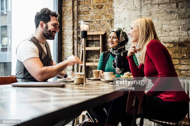Group of friends chatting in coffee shop