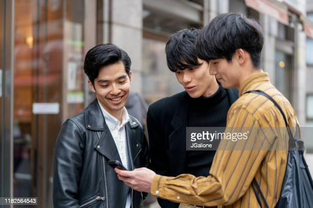 group of friends checking a smartphone outdoors - jgalione stock pictures, royalty-free photos & images