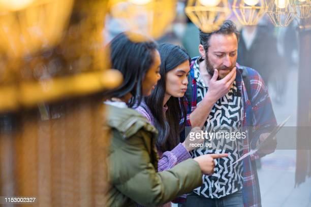 レストランの前でメニューをチェックする友達のグループ - 観光客 ストックフォトと画像