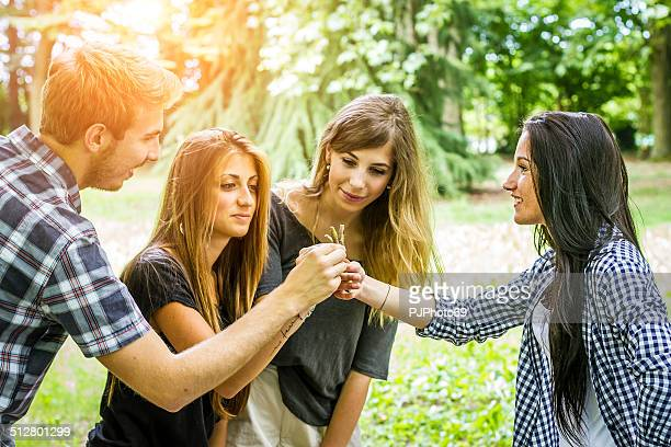 group of friends choosing a stick - pjphoto69 stock pictures, royalty-free photos & images