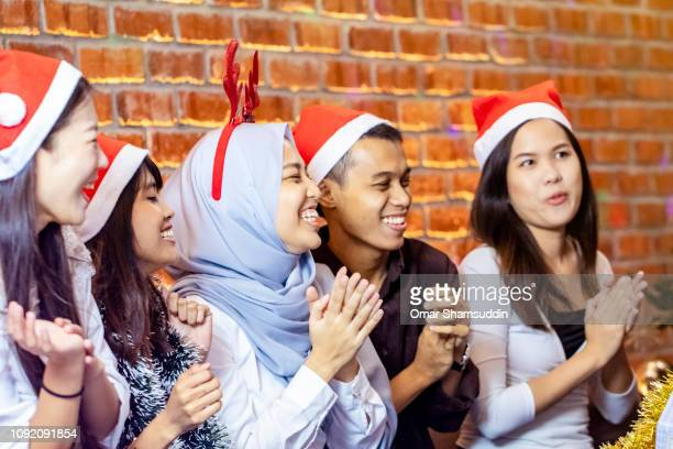 Group of friends clapping hands during Christmas gathering in Kuala Lumpur
