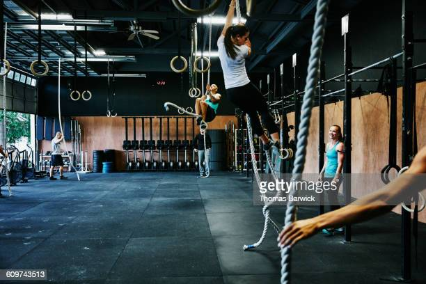 Group of friends climbing ropes in gym gym