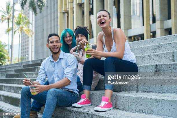 group of friends consisting of two men and two women are sitting on the stairs at the entrance of the university where they study - medellin colombia stock pictures, royalty-free photos & images