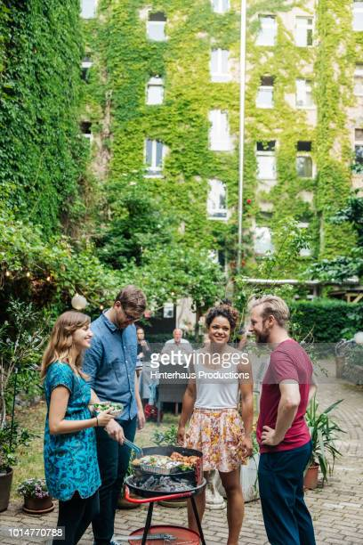 group of friends cooking on bbq in courtyard - adults only stock pictures, royalty-free photos & images