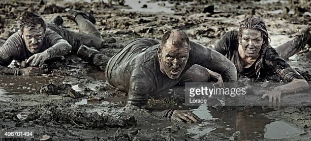 group of friends crawling in mud - obstacle course stock photos and pictures