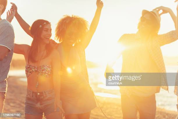 group of friends dancing and celebrating on the beach at sunrise/sunset. - tropical climate stock pictures, royalty-free photos & images