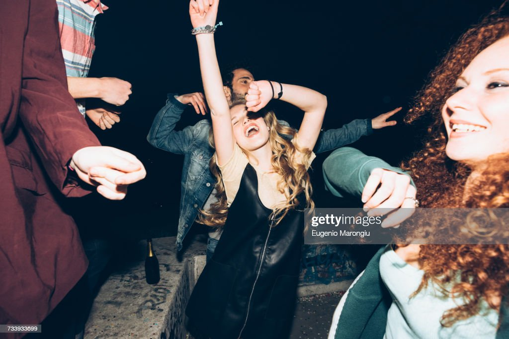 Group of friends dancing, enjoying roof party at night : Stock Photo