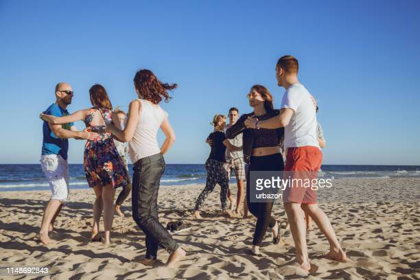 group of friends dancing on the beach - rumba stock photos and pictures