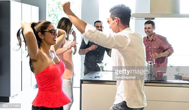 Groupe de amis danser sur la fête dans la cuisine