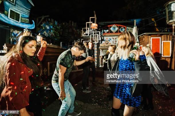 group of friends dancing together at colourful open air nightclub - diskothek stock-fotos und bilder