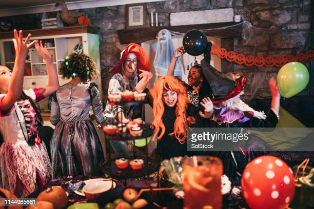 group of friends dancing together - halloween party stock photos and pictures