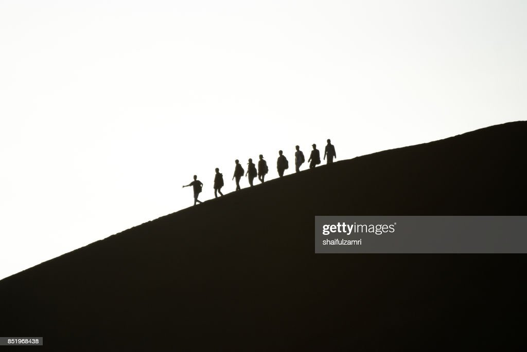 A group of friends descending Mt. Bromo in morning mist. Mt. Bromo is one of the most visited tourist attractions in East Java, Indonesia. : Stock Photo