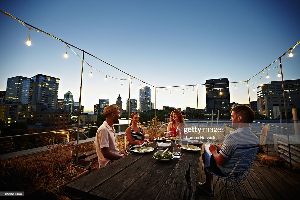 Group of friends dining at table on rooftop deck : Stock Photo