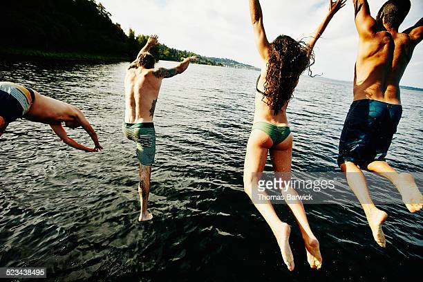 Group of friends diving and jumping into lake