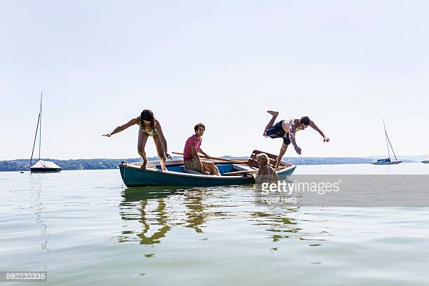 Group of friends diving from boat into lake, Schondorf, Ammersee, Bavaria, Germany