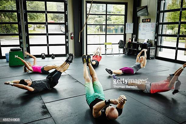 group of friends doing abs workout on floor of gym - asian six pack stock photos and pictures