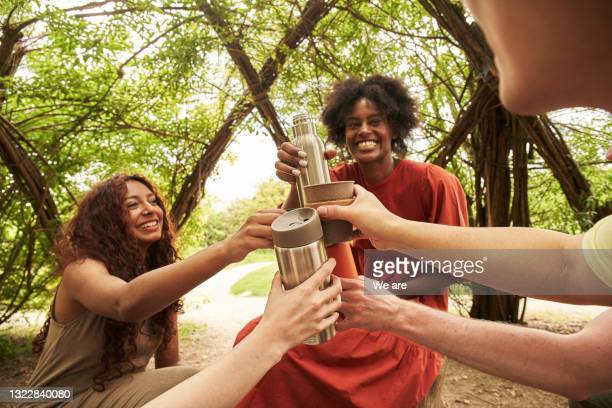 group of friends doing 'cheers' with insulated cups after a long walk in forest - woodland stock pictures, royalty-free photos & images