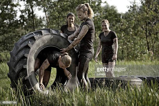 group of friends doing tyre obstacle during mud run