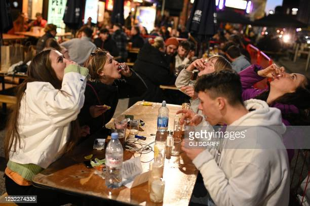 Group of friends drink tequila at a table outside a bar in the Northern Quarter of central Manchester, on April 12, 2021 as coronavirus restrictions...