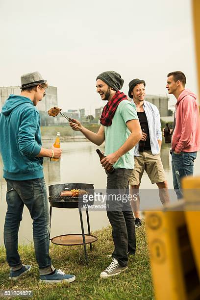 Group of friends drinking beer and having a barbecue