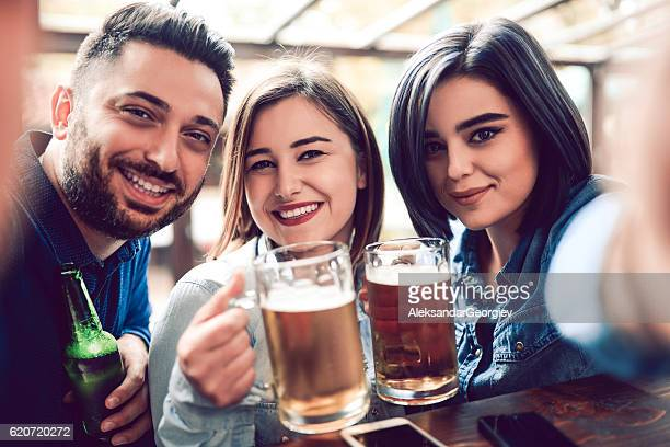 Group of Friends Drinking Beer at Bar and Taking Selfie