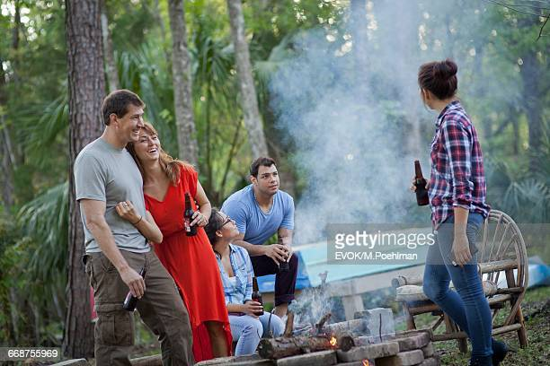 Group of friends drinking beer by campfire