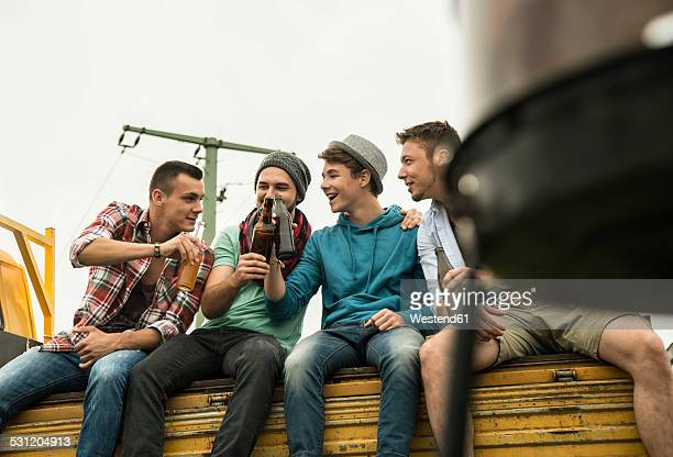 Group of friends drinking beer on pick-up truck