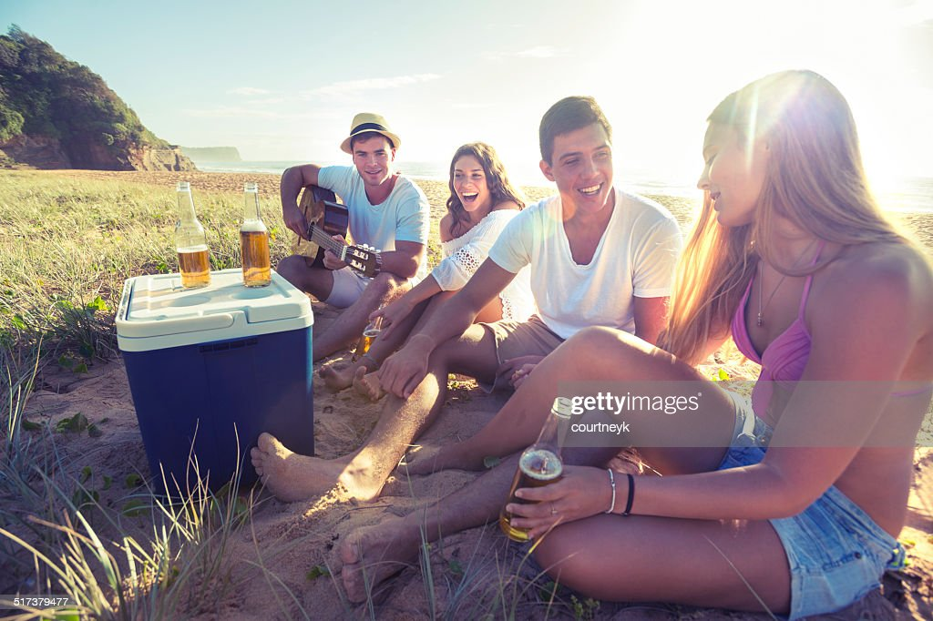Group of friends drinking beer on the beach : Stockfoto