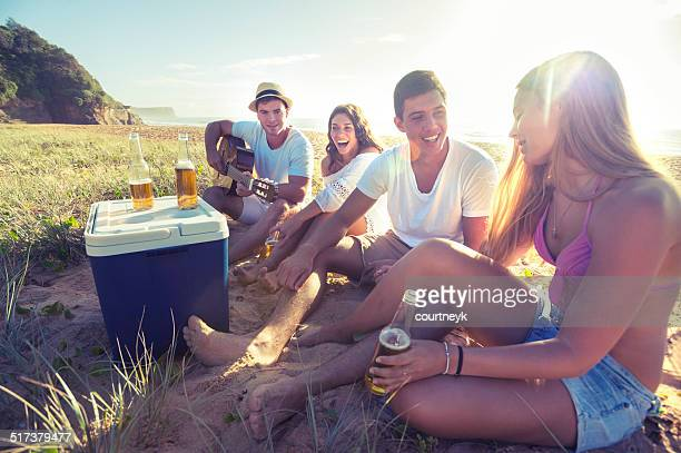 Group of friends drinking beer on the beach