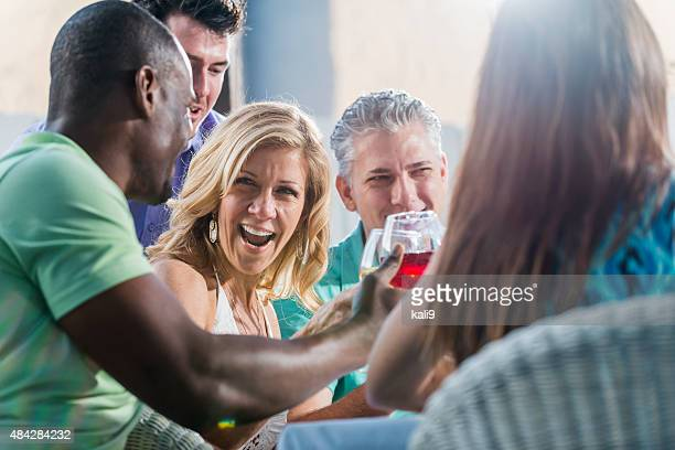 Group of friends drinking wine at party toasting