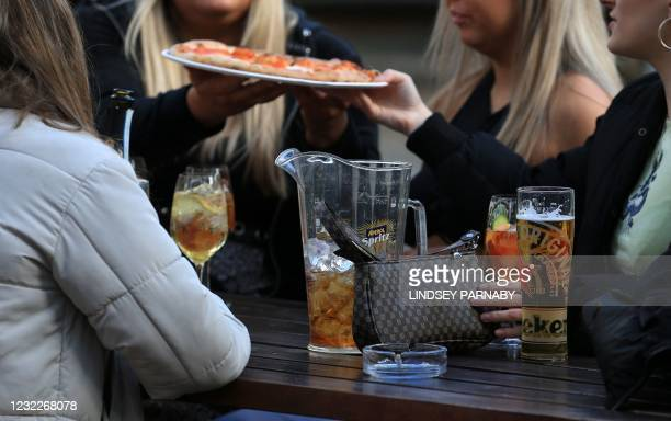 Group of friends eat pizza at a table outside the Water Lane Boathouse bar in Leeds, northern England on April 12 as coronavirus restrictions are...
